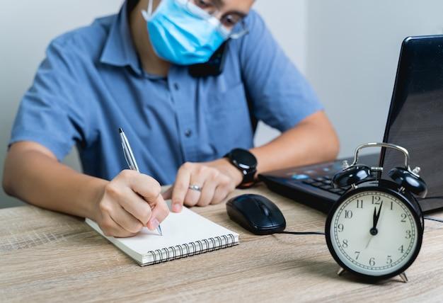 Werk vanuit huis tijdens het uitbreken van het virus. om middernacht werkte de zakenman vanuit huis, hij was aan het telefoneren en noteerde de informatie in het bedrijfsconcept.