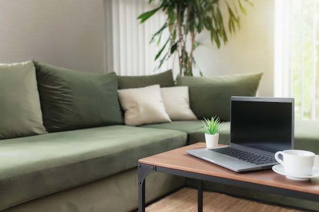 Werk vanuit huis, werkruimte, desktop, extern werkconcept, grijze dunne laptopcomputer met zwart leeg scherm op bruin houten tafel met witte kop koffie, groene bank, bloempot. comfortzone appartement