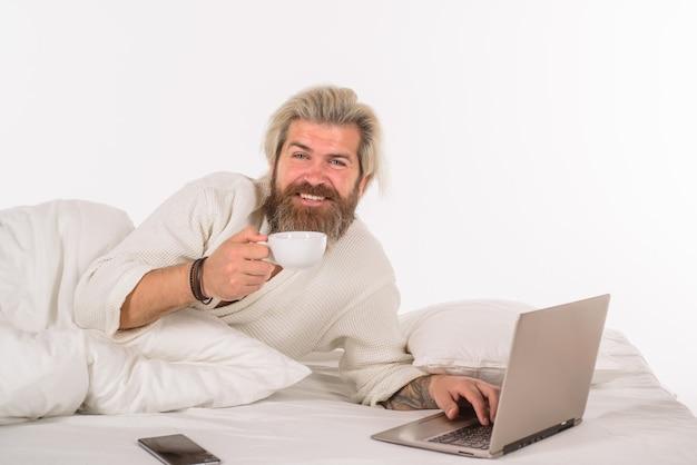 Werk vanuit huis zelfisolatie man met laptop aan het werk in bed man met laptop en smartphone