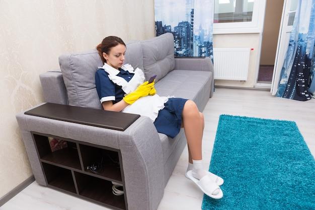 Werk verlegen huishoudster of meid die een pauze neemt zittend op een comfortabele bank in haar uniform en rubberen handschoenen die haar mobiele telefoon checkt