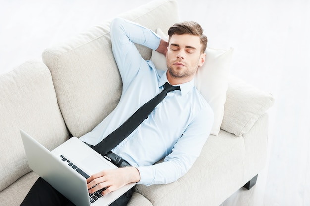 Werk waar hij slaperig van wordt. bovenaanzicht van jonge zakenman die slaapt en hand achter het hoofd houdt
