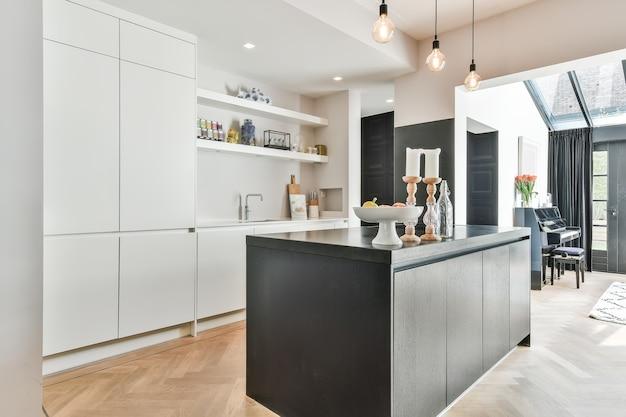 Werkbladen met fornuis en oven gelegen in moderne keuken bij eetkamer thuis