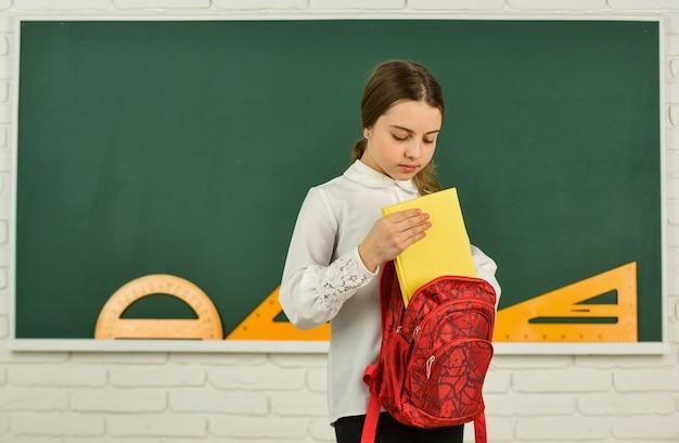 Werkboek om te schrijven. wiskunde les klas. slim hipster tienerkind. kind klaar om te studeren. toerist of student. reizen voor onderwijs in het buitenland. terug naar school. gelukkig meisje draagt rugzak op blackboard.