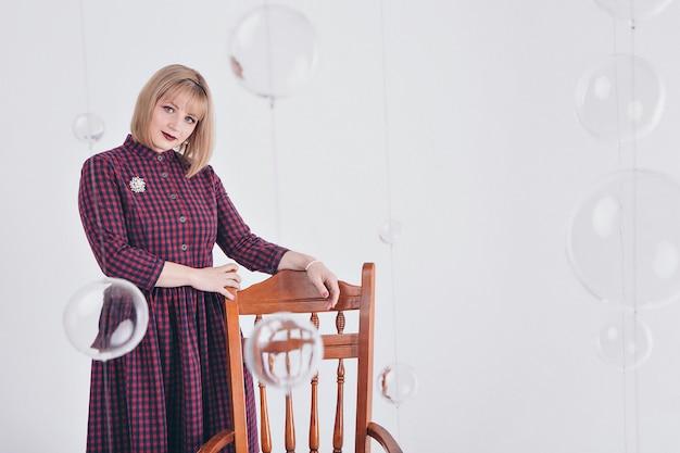 Werkconcept, modelzaken - modieus modieus portret van een vrouw met wit kort haar. model in paarse jurk met broche zittend op een stoel op witte achtergrond