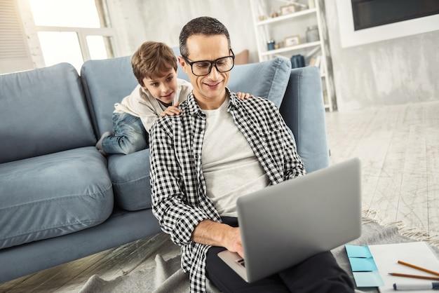 Werkdag. knappe gelukkig donkerharige vader die een bril draagt en op de laptop werkt en zijn zoon achter hem zit