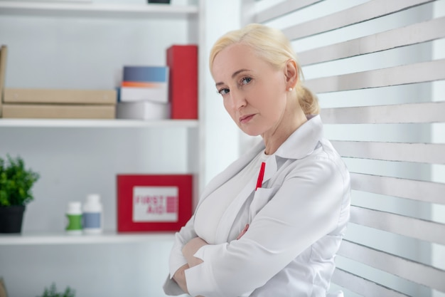 Werkdagen. succesvolle vrouw in een medische jas staande in het kantoor met haar rug naar het raam gevouwen handen op haar borst.
