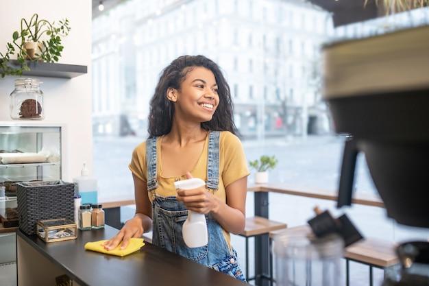 Werkdagen. vrolijk lachende jonge vrouw afvegen oppervlak met servet in café afgeleid op zoek naar kant
