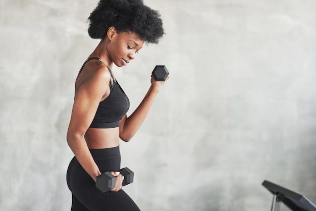 Werken aan biceps. studio shot van jonge vrouw die voor grijze achtergrond staat met halters in handen