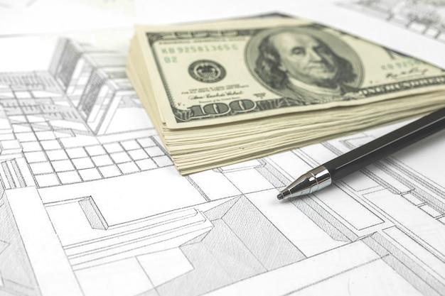 Werken aan bouwproject achtergrond. kantoortafel met dollars en pen op schetsen