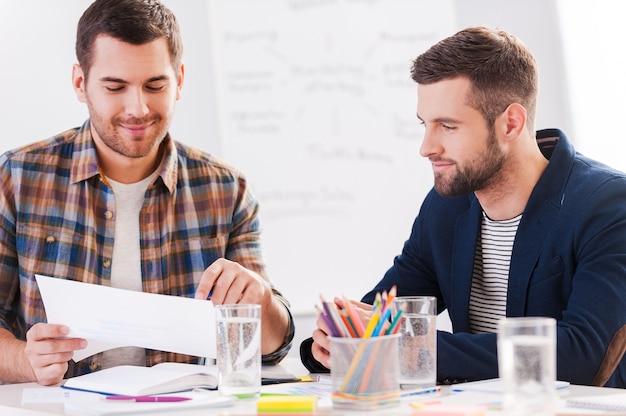 Werken aan creatief project. twee zelfverzekerde zakenmensen in slimme vrijetijdskleding die samen aan tafel zitten en iets bespreken