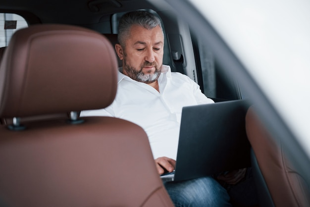 Werken aan een achterkant van de auto met behulp van zilverkleurige laptop. senior zakenman