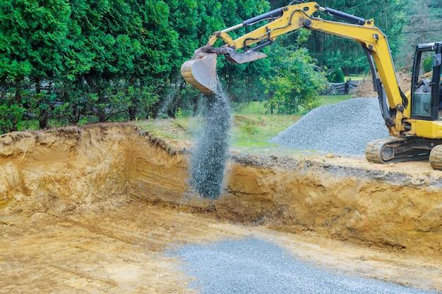 Werken aan een bouwgraafmachine die grindstenen beweegt voor de funderingsbouw