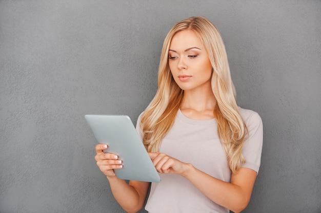 Werken aan haar gloednieuwe tablet. zelfverzekerde jonge vrouw die aan digitale tablet werkt