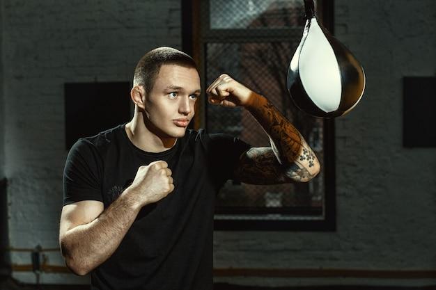 Werken aan zijn snelheid. horizontaal schot van een jonge mannelijke bokser die met de speedbag oefent