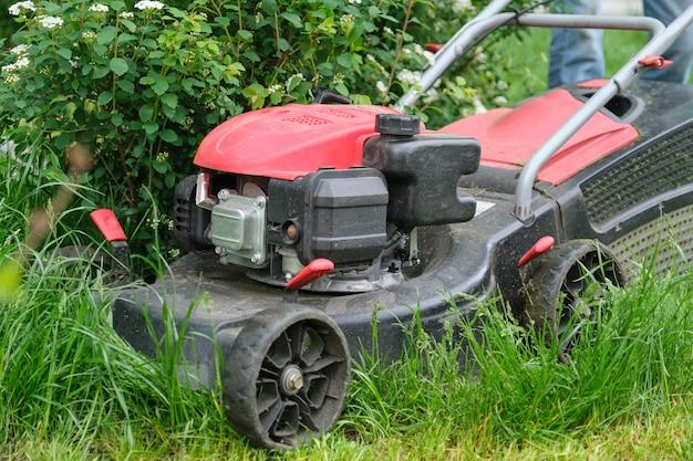 Werken grasmaaier op groen gazon met bijgesneden gras