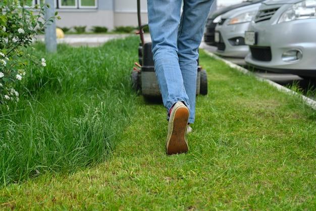 Werken grasmaaier op groen gazon met bijgesneden gras.