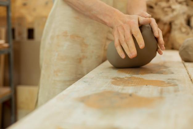 Werken in atelier. hardwerkende sterke man die een groot deel van de klei drukt terwijl hij een basisfiguur vormt