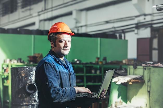Werken in de fabriek met een laptop in de hand op de achtergrond van de apparatuur