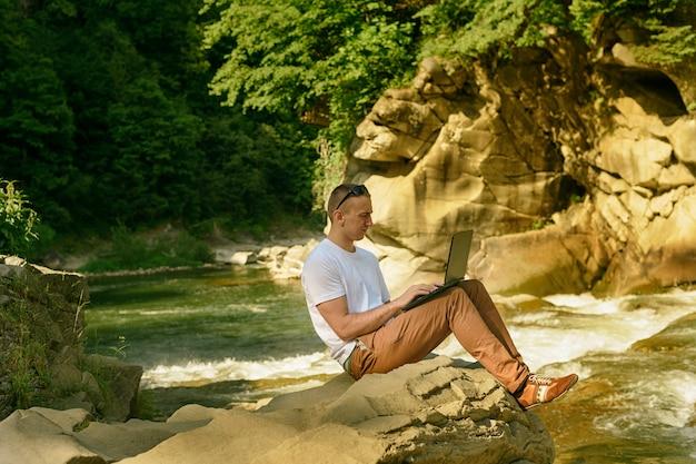 Werken in de natuur concept. man met laptop zittend aan de oever van de rivier over de waterval en groene bomen. zijaanzicht