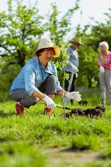 Werken in de tuin. gepensioneerde vrouw met een mooie zomerhoed die in de tuin bij haar vrienden werkt