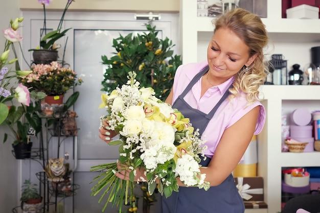 Werken in een bloemenwinkel. professionele bloemist maakt een enorm mooi boeket van verse witte rozen, gele lelies en groene bladeren. verkoper op haar werkplek in uniform met bloemenbos.