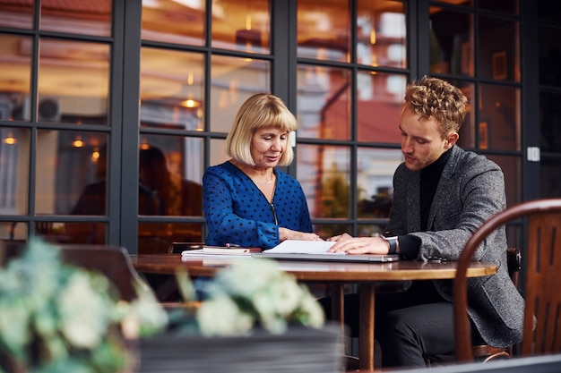 Werken met documenten. jonge kerel in formele kleding heeft een zakelijk gesprek met oude vrouw in café.