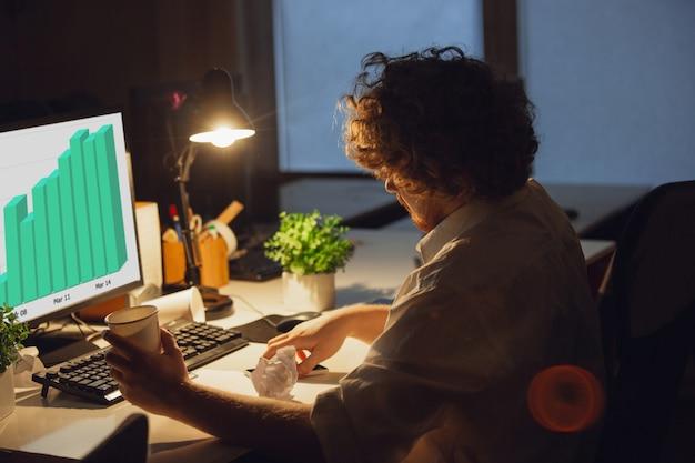 Werken met grafieken. man aan het werk op kantoor, tot laat in de nacht.