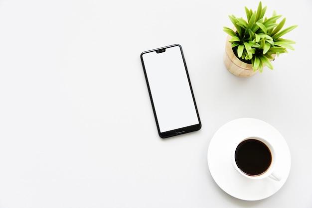 Werken met smartphone, hete koffie en plant kopie ruimte op bureau achtergrond