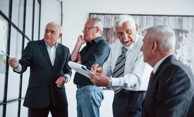 Werken met stickers op glas. leeftijd team van oudere zakenman architecten hebben een vergadering op kantoor.