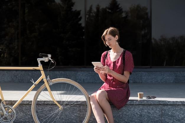 Werken met technologie buiten kantoor. jonge vrouw in stijlvolle retro jurk werken met een tabletcomputer buiten in stedelijk gebied, naast een woon-fiets