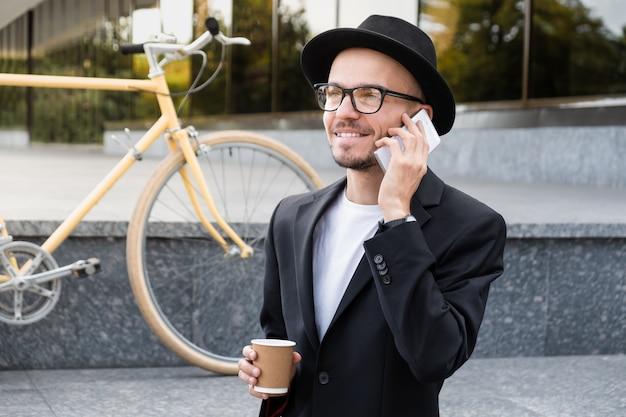 Werken met technologie out of office concept. portret van een jonge man in casual pak praten aan de telefoon in stedelijk gebied
