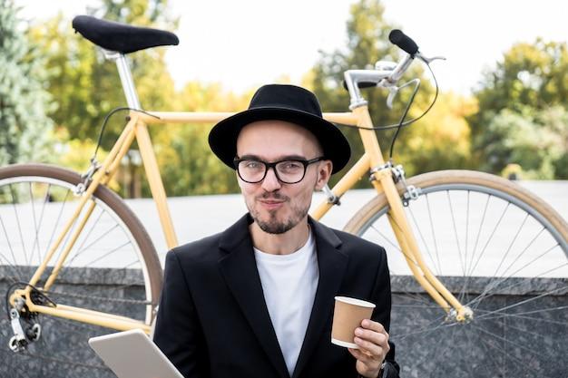 Werken met technologie out of office concept. portret van een jonge man met grappige vrolijke gezichtsuitdrukking in stijlvolle casual kleding, zittend met koffie en tablet-computer buitenshuis