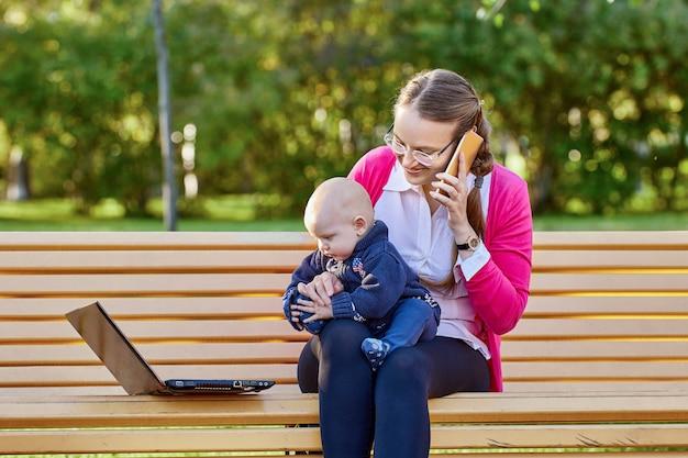 Werken op afstand door vrouw met baby met laptop op parkbank
