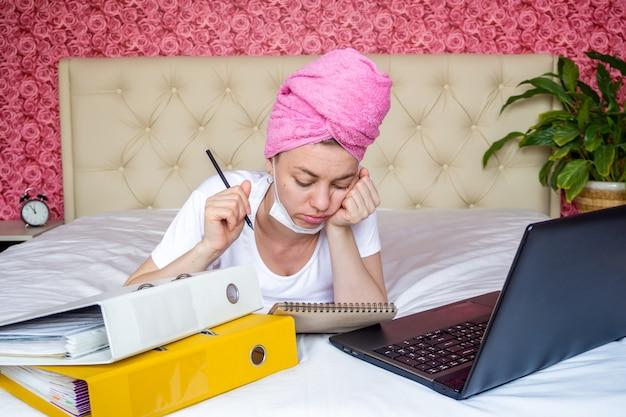 Werken op afstand vanuit huisquarantaine. verveeld jong kaukasisch meisje in een masker dat huiswerk met laptop doet. ziet er triest uit en maakt aantekeningen in een notitieboek.