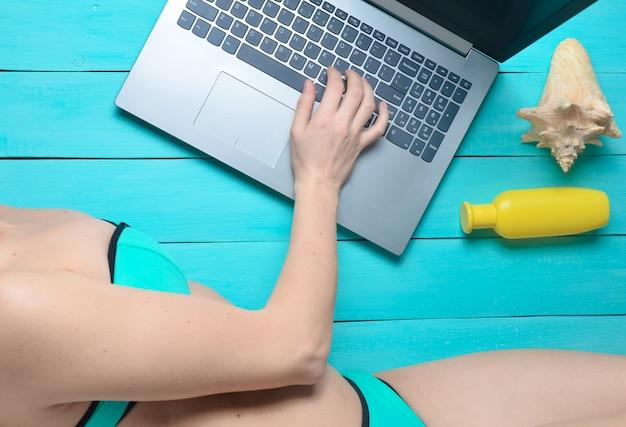 Werken op afstand voor een laptop in een badplaats. een meisje in een zwembroek gebruikt een laptop. accessoires voor ontspanning op het strand: zonnebril, sunblock, koptelefoon, schelp.