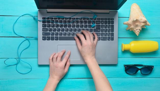 Werken op afstand voor een laptop in een badplaats. vrouwelijke handen typen de tekst op het toetsenbord. accessoires voor ontspanning op het strand: zonnebril, sunblock, koptelefoon, schelp.