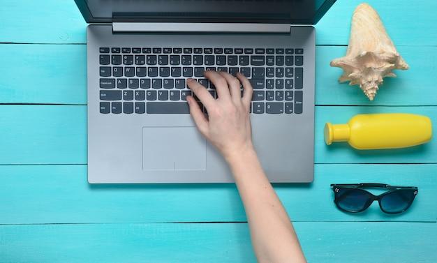 Werken op afstand voor een laptop in een badplaats. vrouwelijke handen typen de tekst op het toetsenbord. accessoires voor ontspanning op het strand: zonnebril, sunblock, schelp. bovenaanzicht.