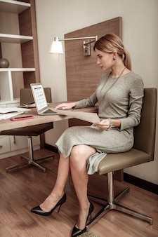 Werken op laptop. blond-haired succesvolle vrouw die kleding en toebehoren draagt die aan laptop werken