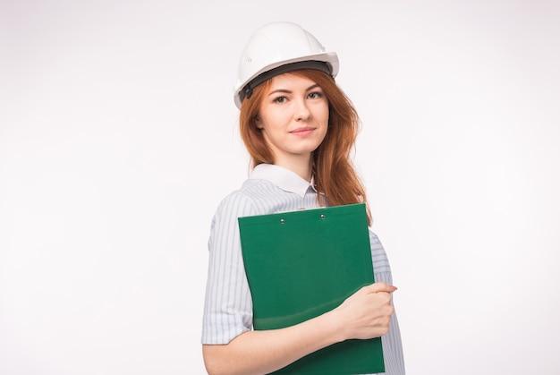 Werken, techniek, mensen concept - een vrouwelijke ingenieur in een helm met bestand over de witte achtergrond.