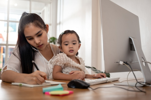 Werken vanuit huis concept. moeder en dochter met behulp van een computer en internet tijdens moeder thuiswerken