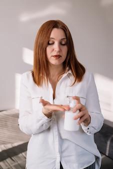 Werken vanuit huis, corona-virusbescherming, close-up die haar handen schoonmaakt met ontsmettingsgels