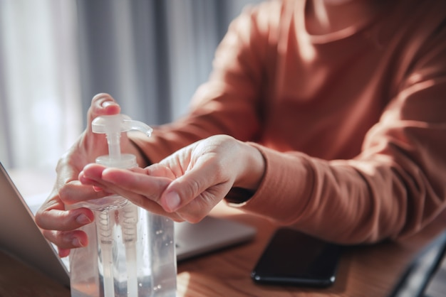 Werken vanuit huis, coronavirus-bescherming, close-up die haar handen reinigt met ontsmettingsgels, vrouw in quarantaine voor coronavirus met beschermend masker.