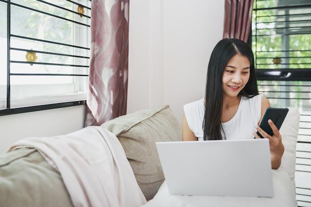 Werken vanuit huis en online winkelen concept, gelukkige aziatische bedrijfsvrouw met behulp van mobiele telefoon en laptopcomputer met laptop op de bank in de huiskamer