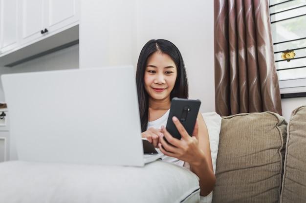 Werken vanuit huis en online winkelen concept, gelukkige aziatische bedrijfsvrouw met behulp van mobiele telefoon en laptopcomputer met laptop op sofa in de huiskamer