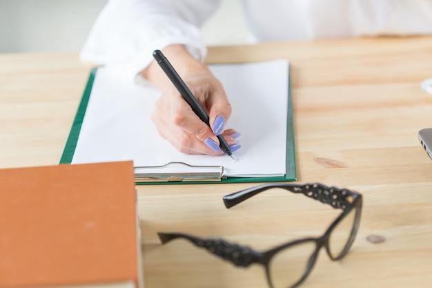 Werken, zaken, kantoorconcept - close-up van de hand wat notities schrijven en een bril erbij liggen