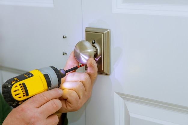Werkend als klusjesman installeer een nieuw deurslot in de kamer