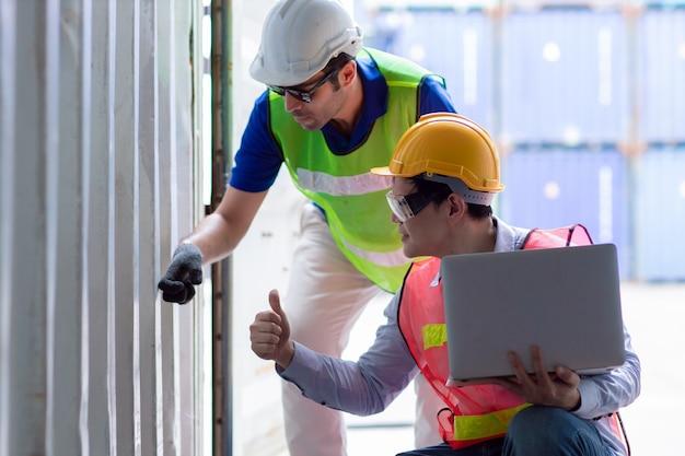 Werkend audit-ingenieursteam in de scheepvaarthaven die de sterktetest van de vrachtcontainer controleert op veiligheid en beveiliging volgens de norm voor intermodale containers.