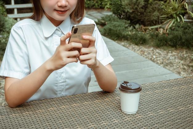 Werkend buitenconcept een vrouwelijke tiener die vredig in een tuin met veel groene bomen zit terwijl ze haar apparaat op internet gebruikt.