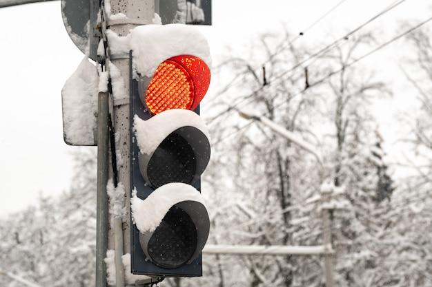 Werkend verkeerslicht op een straat in de stad in de winter het rode lampje van het verkeerslicht brandt