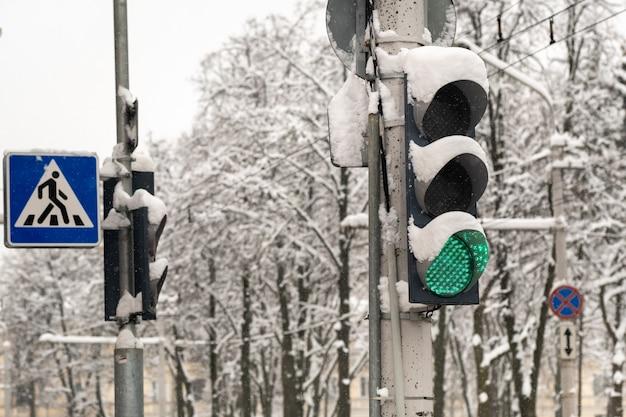 Werkend verkeerslicht op een straat in de stad in de winter het verkeerslicht is groen